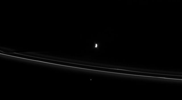 NASA's Cassini spacecraft captured this view on Apr. 8, 2008, showing two of Saturn's moons, Daphnis and Prometheus, and their gravitational effects on nearby rings.