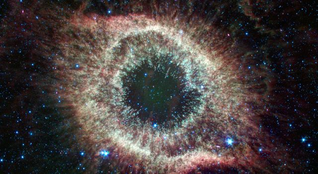 A newly expanded image of the Helix nebula lends a festive touch to the fourth anniversary of the launch of NASA's Spitzer Space Telescope