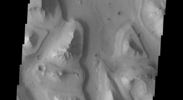 This image from NASA's Mars Odyssey spacecraft shows different levels of downcutting giving a stepped appearance to the mesas in this region of Hydroates Chaos on Mars.
