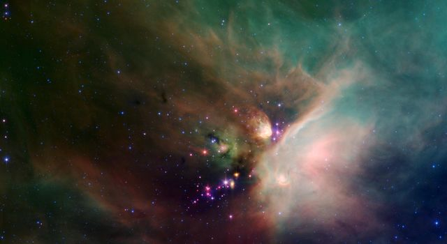 Newborn stars peek out from beneath their natal blanket of dust in this dynamic image of the Rho Ophiuchi dark cloud from NASA's Spitzer Space Telescope.