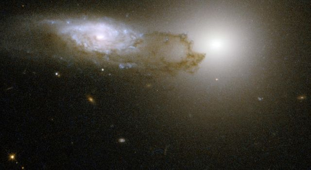 AM 1316-241 is made up of two interacting galaxies—a spiral galaxy (on the left of the frame) in front of an elliptical galaxy (on the right of the frame). This image is part of a large collection of images of merging galaxies taken by NASA's Hubble.
