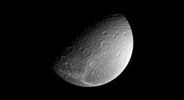 This view from NASA's Cassini spacecraft was taken from a vantage point 64 degrees above Saturn's moon Dione's equator, looking down onto the bright fractures that cover the moon's trailing side.