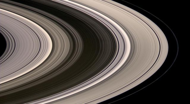 Saturn's icy rings shine in scattered sunlight in this view captured by NASA's Cassini spacecraft shows, looking toward the unilluminated northern side of the rings from above the ringplane. The inner F-ring shepherd moon Prometheus appears at lower left.