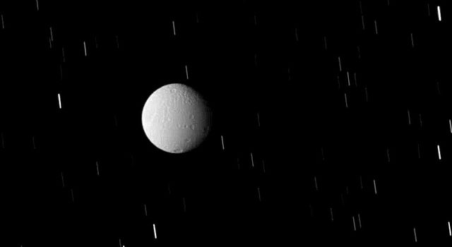 Tethys sits within Saturn's shadow, but not in complete darkness as shown in this image captured by NASA's Cassini spacecraft on Sept. 25, 2008.