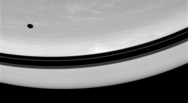 The shadow of Tethys drifts across the face of Saturn. Nearby, shadows of the planet's rings form a darkened band above the equator in this image captured by NASA's Cassini spacecraft on Oct. 1, 2008.