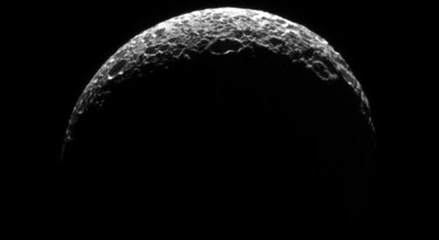 Saturn's moon Mimas's lit crescent has the appearance of a golf ball thanks to its heavily cratered surface in this image captured by NASA's Cassini spacecraft on Oct. 24, 2008.