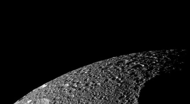 The terminator encroaches upon Penelope, one of the largest craters on Saturn's moon Tethys. Two other large craters, Polyphemus and Phemius, are visible near the limb in this image from NASA's Cassini spacecraf taken on Nov. 24, 2008.