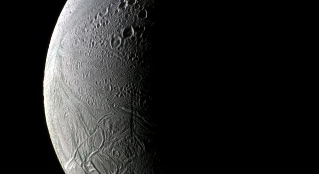 Sunrise uncovers both old and new Enceladus in this image from NASA's Cassini spacecraft. The lit side of the moon faces Saturn toward the left in this view of the trailing hemisphere.