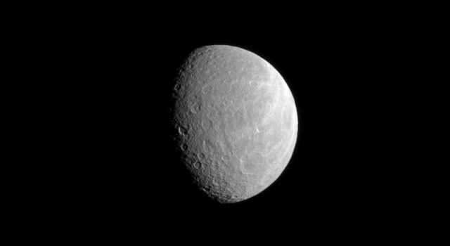 A wide crater dominates the lower right of this image while part of Rhea's brightly lit, wispy terrain can still be seen near the limb of the moon. This image was taken in visible light with NASA's Cassini spacecraft's narrow-angle camera.