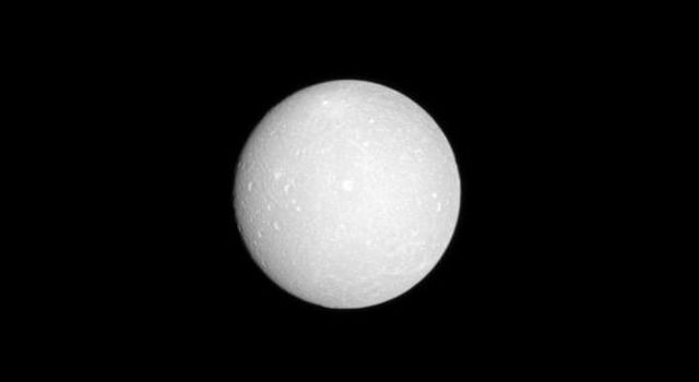 The face of Saturnian moon Dione is almost fully lit as NASA's Cassini spacecraft flies in between this moon and the sun with Dione at low phase. With a few hundred pixels of its digital camera, Cassini details dozens of craters a million kilometers away.