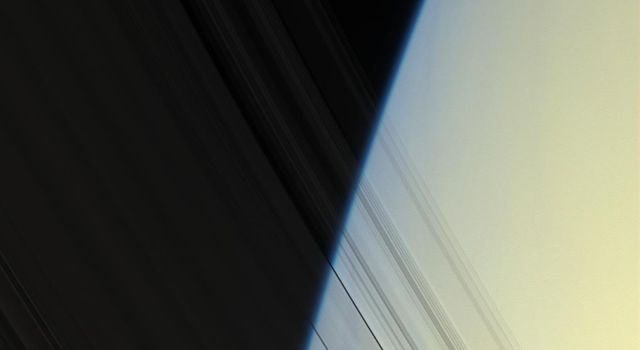 NASA's Cassini spacecraft peers through Saturn's delicate, translucent inner C ring to see the diffuse blue limb of Saturn's atmosphere in this image taken on April 25, 2008.