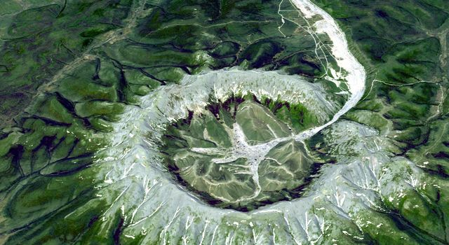 The Kondyor Massif is located in Eastern Siberia, Russia, north of the city of Khabarovsk. It is a rare form of igneous intrusion called alkaline-ultrabasic massif and it is full of rare minerals. This image is from NASA's Terra satellite.