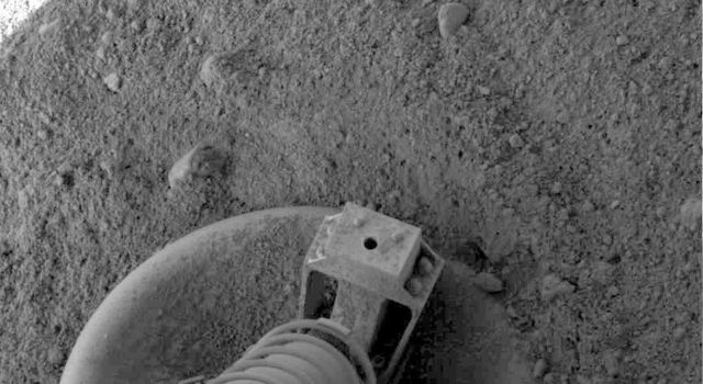NASA's Phoenix Mars Lander did a small amount of excavation as it touched down on pebbly north polar terrain on the Red Planet, as shown in this close-up view of one of the lander's three footpads.