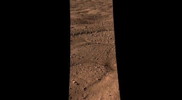 This image shows the vast plains of the northern polar region of Mars, as seen by NASA's Phoenix Mars Lander shortly after touching down on the Red Planet. The flat landscape is strewn with tiny pebbles and shows polygonal cracking.