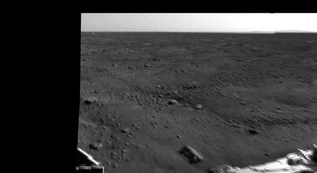This image zooms in on the backshell and parachute, about 300 meters to the south of NASA's Phoenix Mars Lander. In the distance, about 9 miles or 15 kilometers away, is a range of hills..