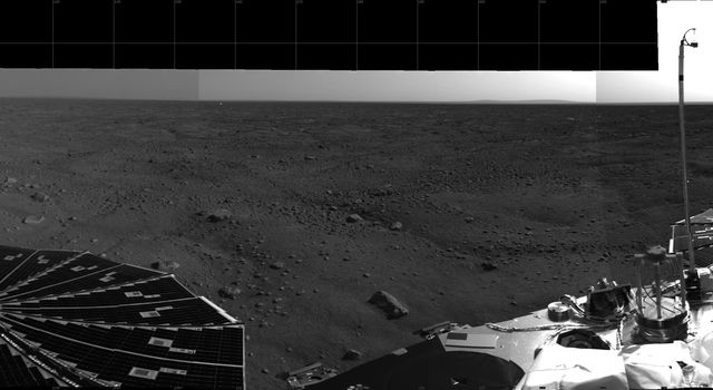This 360-degree view from NASA's Phoenix Mars Lander shows the spacecraft's solar arrays, lander deck and the Martian polar landscape beyond. The hummocky terrain has a network of troughs and very few rocks.