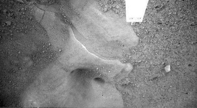 NASA's Phoenix Mars Lander shows a detailed image of the feature informally called 'Snow Queen,' located just beneath the lander. The holes in the image are located under Phoenix's thrusters.