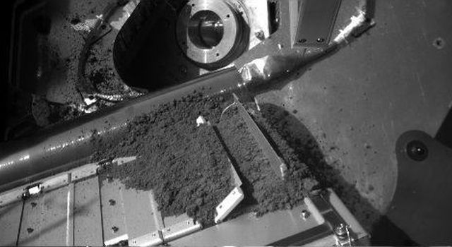 The Robotic Arm of NASA's Phoenix Mars Lander released a sample of Martian soil onto a screened opening of the lander's Thermal and Evolved-Gas Analyzer (TEGA) during the 12th Martian day, or sol, since landing (June 6, 2008).