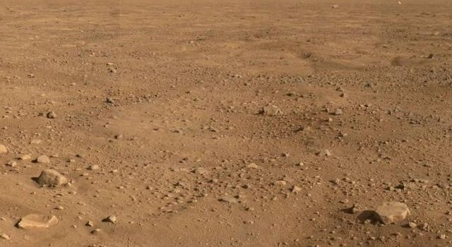 This panorama looks to the southeast and shows rocks casting shadows, polygons on the surface and as the image looks to the horizon, NASA's Phoenix Mars Lander's backshell gleams in the distance.
