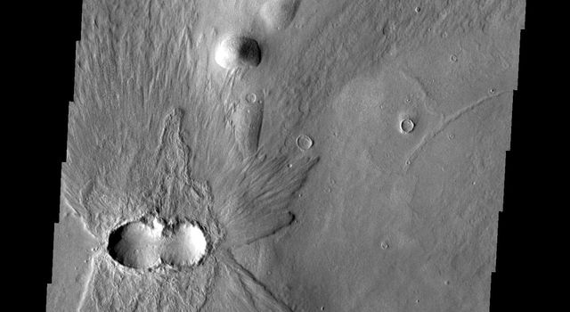 This image from NASA's Mars Odyssey shows ejecta pattern and double crater indicate that two impactors on Mars hit at the same time. The ejecta pattern and doublet crater look like a fancy butterfly flying west.