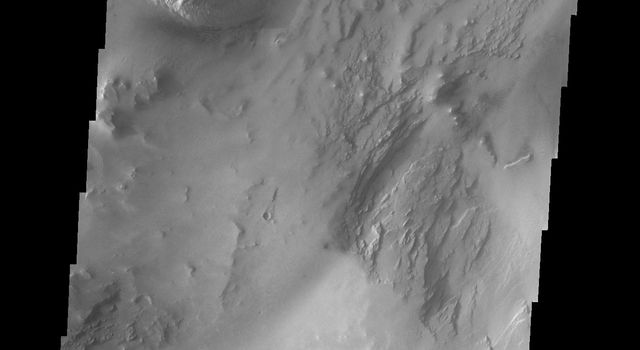 This image from NASA's Mars Odyssey shows some of the floor deposits within Candor Chasma on Mars. These deposits have been eroded by wind, and possibly by water.