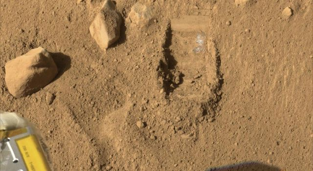 This image of the trench shows a white layer that has been uncovered by the Robotic Arm (RA) scoop onboard NASA's Phoenix Mars Lander and is visible in the wall of the trench.