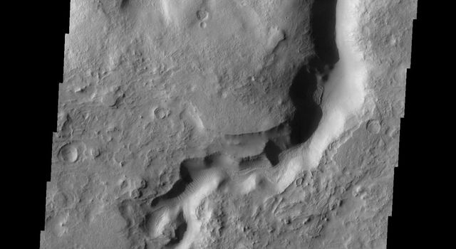 This image from NASA's Mars Odyssey shows the eastern and northern margins of Terra Sabaeaon Mars, heavily dissected by channels and fractures. This channel is one example of the many found in this region. Dunes are located on the floor of the channel.