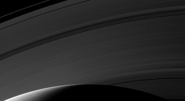 Day breaks on the northern hemisphere of Saturn in this image from NASA's Cassini spacecraft taken on Mar. 20, 2009. The D ring is hidden below the horizon, but, this image shows the C, B, A and F rings.