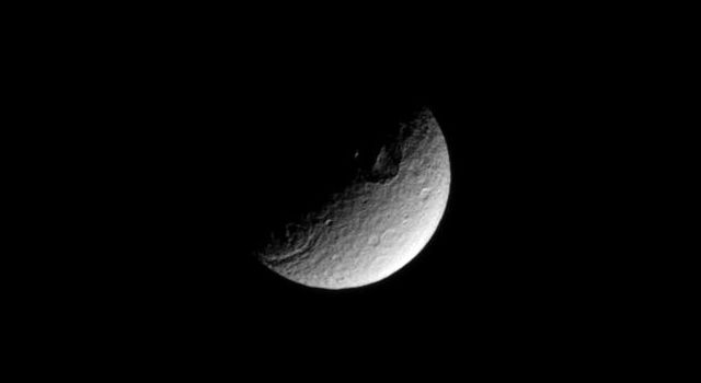 The terminator between shadow and light cuts across a large crater in the high southern latitudes of the moon Tethys in this image taken by NASA's Cassini spacecraft taken on Feb. 16, 2009.