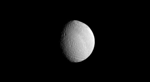The huge Odysseus Crater disfigures the face of Saturn's moon Tethys in this image taken by NASA's Cassini spacecraft taken on Apr. 24, 2009.