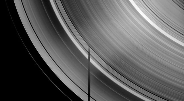 The tip of the shadow of the moon Tethys is cut off where it crosses Saturn's B ring, demonstrating the variations in density across the planet's rings in this image taken by NASA's Cassini spacecraft taken on Apr. 29, 2009.