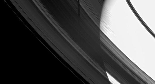 The shadow of the moon Tethys is revealed on Saturn's B and C rings in this image which also includes the planet.