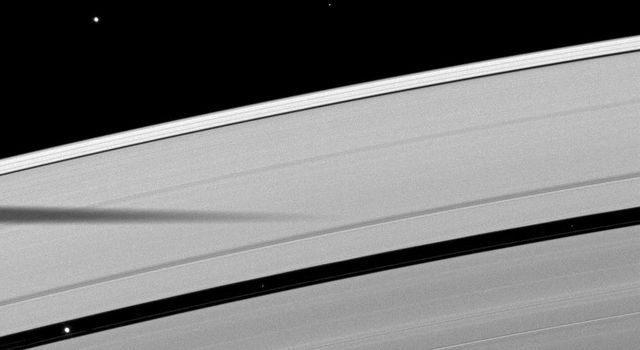 The shadow of the moon Mimas is cast on Saturn's outer A ring in this image which also shows a couple of moons and a collection of stars. This image is from NASA's Cassini spacecraft.