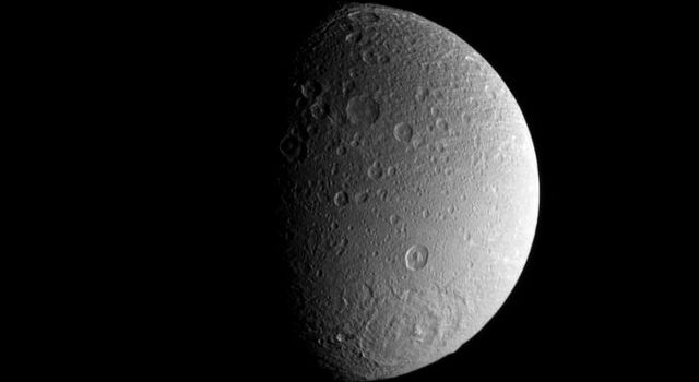 A large impact basin dominates the high southern latitudes of Saturn's moon Dione as seen by NASA's Cassini spacecraft.