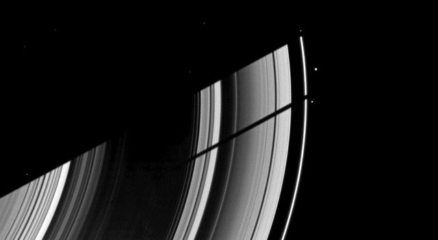 The moon Tethys casts its shadow on Saturn's rings next to the shadow of the planet in this image taken as Saturn approaches its August 2009 equinox. This image is from as seen by NASA's Cassini spacecraft.