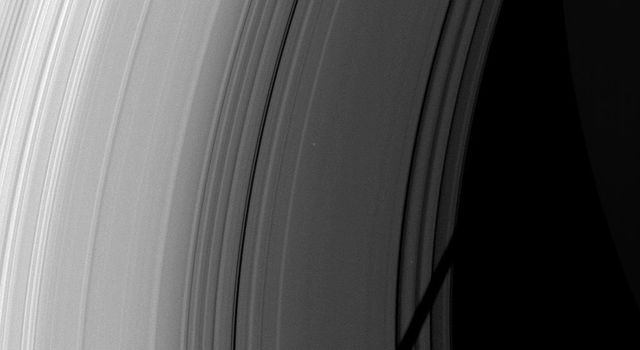 The shadow of Saturn's icy moon Tethys cuts across the C ring in this image taken as Saturn approaches its August 2009 equinox as seen by NASA's Cassini spacecraft.
