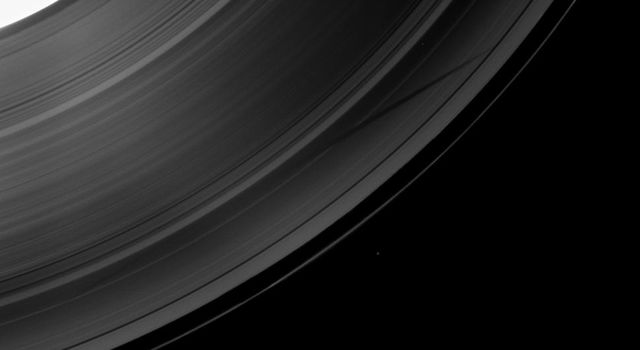 NASA's Cassini spacecraft shows a section of Saturn and its rings which includes a special treat made possible as the planet approaches its August 2009 equinox: the shadow of a moon cast on the rings.