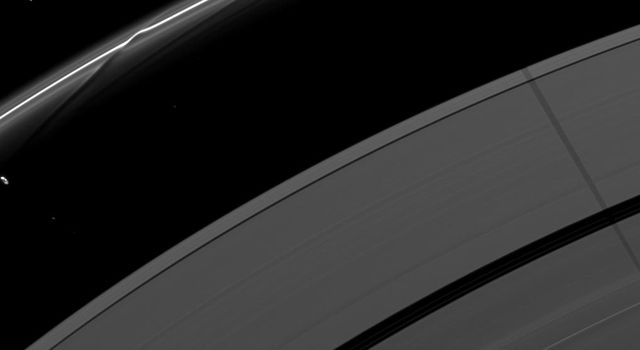 Saturn's moon Janus casts a shadow on the F and A rings while the moon Prometheus, seen on the left of the image, creates a streamer-channel in the thin F ring. This image is from as seen by NASA's Cassini spacecraft.