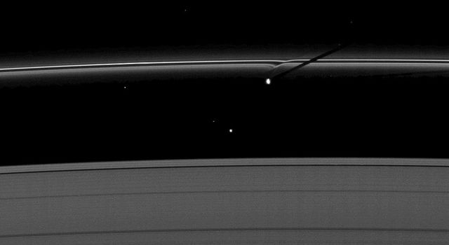 The moon Prometheus casts a shadow on Saturn's F ring near a streamer-channel it has created on the ring. The image was taken by NASA's Cassini spacecraft as the planet approached its August 2009 equinox.