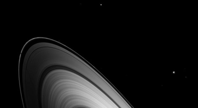 Just before Saturn's August 2009 equinox, Dione joined other Saturnian moons in casting shadows on the planet's main rings as seen by NASA's Cassini spacecraft.