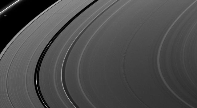 Saturn's moons Prometheus and Pan cast a pair of shadows on the A ring in this image taken shortly after the planet's August 2009 equinox by NASA's Cassini spacecraft. The gravity of potato-shaped Prometheus creates streamer-channels in the F ring.