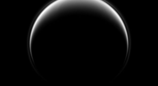 In this image, NASA's Cassini spacecraft looks down on the north pole of Titan, and, although this view is centered on the leading hemisphere of the moon, the lit terrain seen here is mostly on the opposite, trailing hemisphere of the moon.