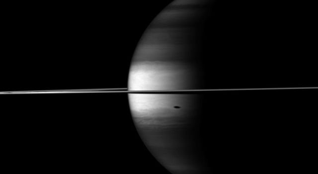 NASA's Cassini spacecraft's camera looks in near-infrared light at a dramatic view of Saturn, its ringplane and the shadows of a couple of its moons.
