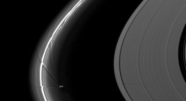 NASA's Cassini spacecraft captured Saturn's moon Prometheus, orbiting near the streamer-channels it has created in the thin F ring, casts a shadow on the A ring in this image taken a little more than a week after the planet's August 2009 equinox.