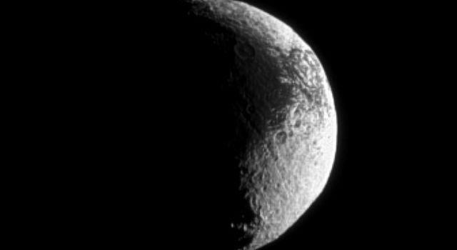 Iapetus shows off its puzzling light and dark terrain in this image captured by NASA's Cassini spacecraft. Lit terrain seen here is on the Saturn-facing side of Iapetus.