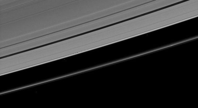 This image, which at first appears to show a serene scene, in fact reveals dramatic disturbances created in Saturn's A ring by its moon Daphnis as seen by NASA's Cassini spacecraft.