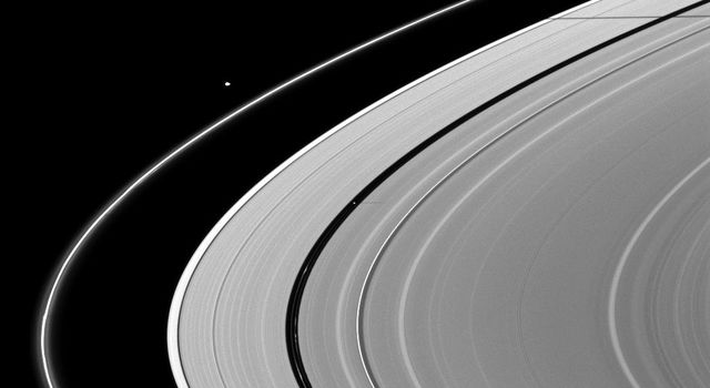 A pair of Saturn's moons, Pan and Janus, cast their shadows on the A ring in this NASA's Cassini spacecraft image taken about a month and a half after Saturn's August 2009 equinox.