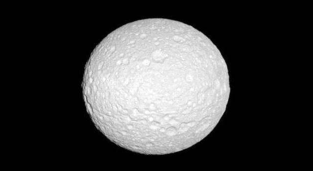 NASA's Cassini spacecraft reveals the cratered surface of Mimas, a moon whose shape is flattened at the poles.