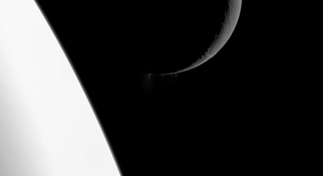 NASA's Cassini spacecraft captures this scene showing the bright crescent of Saturn's moon Enceladus at top right. The center of the image reveals plumes of water ice spew out from fractures known as 'tiger stripes' near the south pole of the moon.