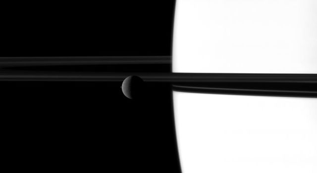 The small moon Janus overtakes the larger moon Rhea in a dance played out before Saturn and its rings in this image taken by NASA's Cassini spacecraft. Go to the Photojournal to view the animation.